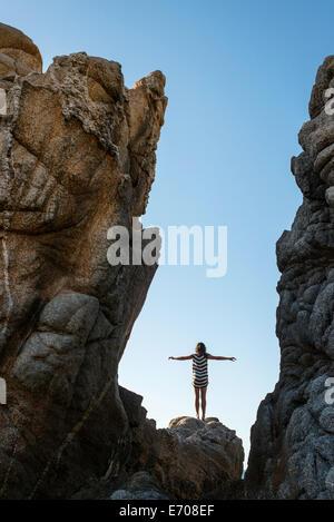 Jeune femme debout sur des rochers sur la plage, les bras tendus