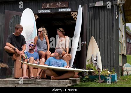 Cinq jeunes surfeurs adultes friends chatting en dehors de shed Banque D'Images