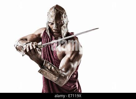 Studio portrait of muscular young man dressed comme gladiator avec casque et épée Banque D'Images