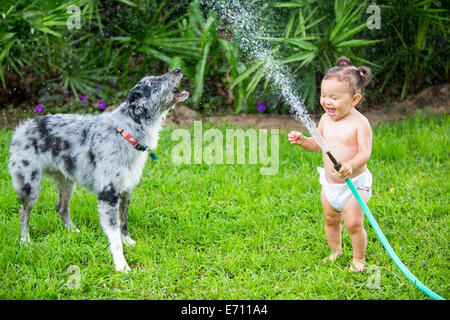 Girl holding tuyau d'eau, Playing with dog Banque D'Images