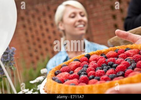 Deux amies avec fruit flan at garden party Banque D'Images