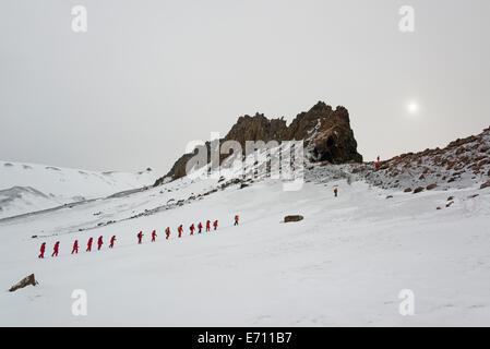 Les voyageurs dans l'imperméable de couleur orange vif en marche une ligne à travers la neige sur l'île Déception. Banque D'Images