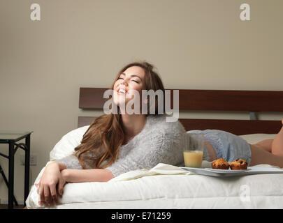 Belle jeune femme en riant on hotel bed Banque D'Images