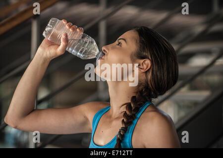 Jeune femme à boire l'eau de bouteille Banque D'Images