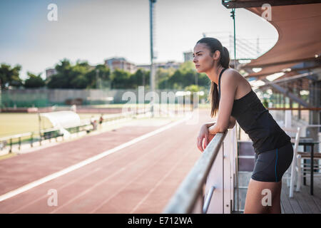 Young woman leaning on railing par race track Banque D'Images