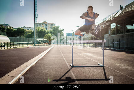 Mid adult man jumping over obstacle Banque D'Images