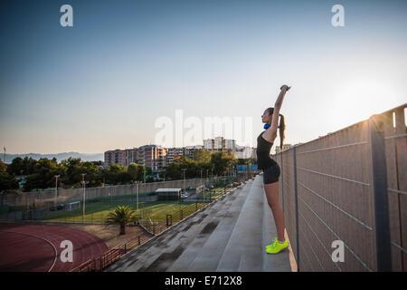 Jeune femme debout sur les mesures qui s'étend les bras
