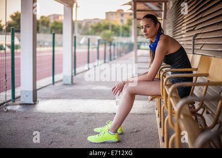 Jeune femme assise sur un banc, le repos Banque D'Images