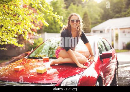 Jeune femme assise sur le capot de voiture, portrait Banque D'Images