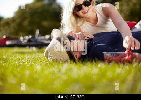 Jeune femme d'atteindre pour les fraises en petit ami couché dans park Banque D'Images