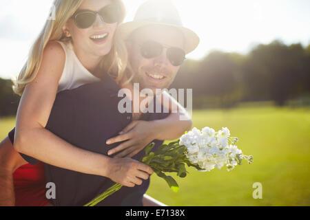 Jeune femme avec des fleurs se greffer de copain dans park Banque D'Images