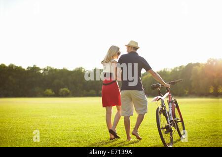 Couple poussant tout en flânant dans le parc à vélo