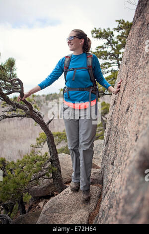 Une jeune femme des randonnées le long d'une falaise dans le Maine Acadia National Park. Banque D'Images