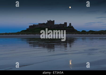 Château de Bamburgh sous une pleine lune au crépuscule en été, Bamburgh, Northumberland, Angleterre, Royaume-Uni, Banque D'Images