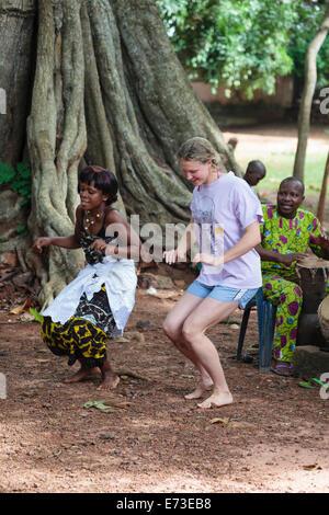 L'Afrique, Bénin, Ouidah. Femme dansant avec danse vaudou au cours de tourisme en face de l'iroko tree in Kpasse Banque D'Images