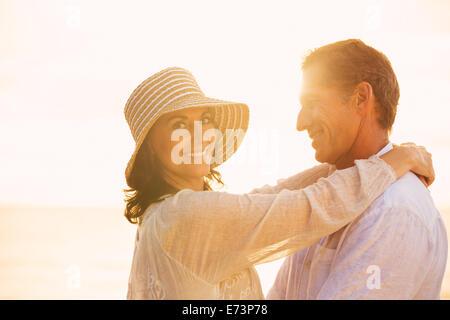 Happy Young Couple in Love sur la plage au coucher du soleil Banque D'Images