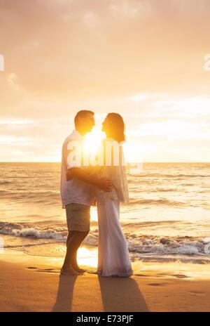 Mature Couple Kissing romantique au coucher du soleil sur la plage Banque D'Images