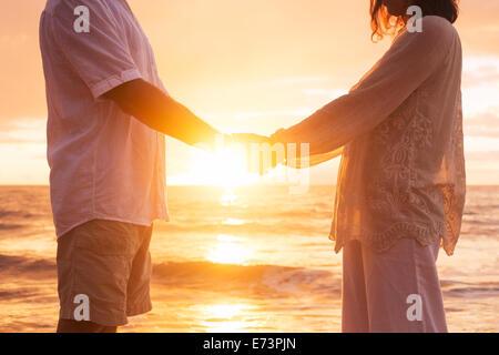Mature romantique Senior Couple Holding Hands bénéficiant au coucher du soleil sur la plage Banque D'Images