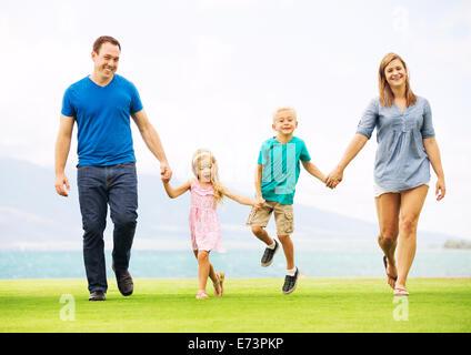 Famille heureuse à l'extérieur sur l'herbe Banque D'Images