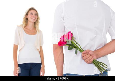 Man hiding bouquet de roses à partir de la femme Banque D'Images