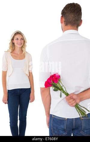 Man hiding bouquet de roses à partir de la jeune femme Banque D'Images