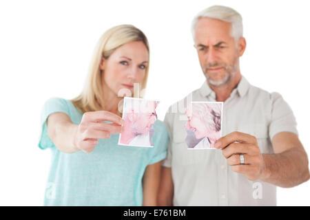 Couple holding deux moitiés de photographie déchirée Banque D'Images