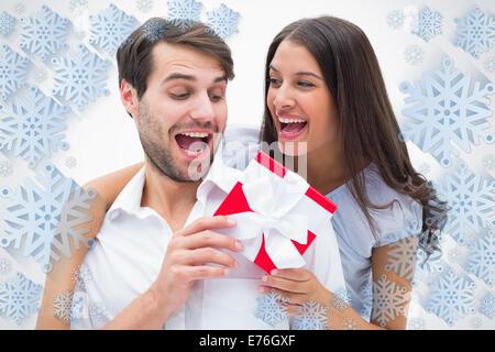 Image composite de jolie brunette étonnant petit ami avec un cadeau Banque D'Images