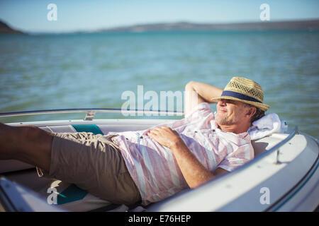 Homme plus âgé se détendre en bateau sur l'eau Banque D'Images