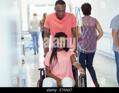 Man wheeling girlfriend in hospital hallway Banque D'Images