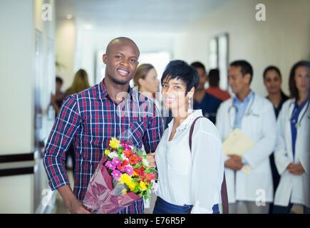 Couple carrying bouquet de fleurs à l'hôpital Banque D'Images