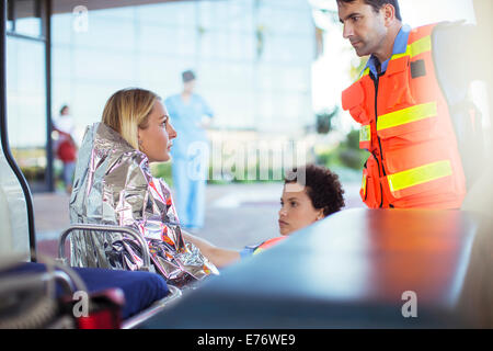 Les ambulanciers parler au patient en ambulance Banque D'Images