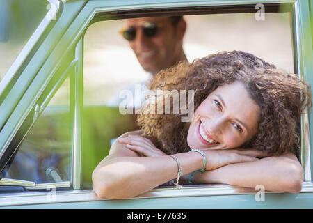 Woman relaxing on porte de la voiture pendant un tour en voiture Banque D'Images