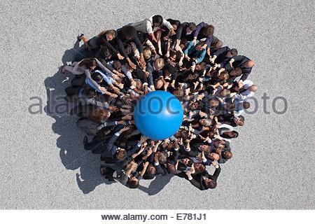 Foule de gens d'affaires de huddle vers de globe Banque D'Images