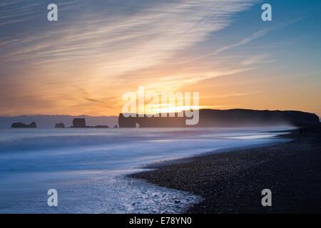 La vue le long de la plage de sable noir de Reynisfjara qui jouit près du village de Vík í Mýrdal vers Dyrhólaey au crépuscule, le sud de l'Islande