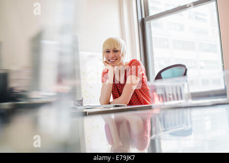 La vie de bureau. Une jeune femme assise dans un bureau 24, le menton reposant sur sa main, regardant la caméra. Banque D'Images