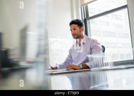 La vie de bureau. Un homme travaillant seul dans un bureau. Banque D'Images