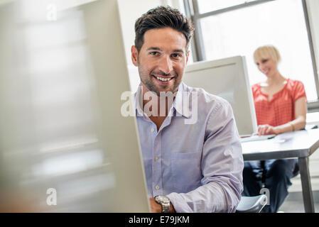 La vie de bureau. Deux personnes assis à un bureau à l'aide d'ordinateurs. Banque D'Images
