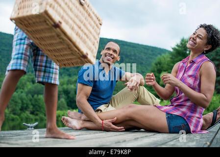 Une famille ayant un pique-nique d'été au bord d'un lac.