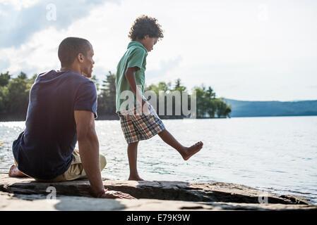 Un père et son fils, sur une rive du lac en été. Banque D'Images