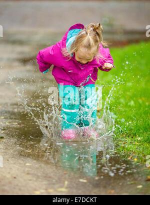 Happy little girl joue dans une flaque Banque D'Images