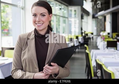 Caucasian businesswoman standing in restaurant Banque D'Images