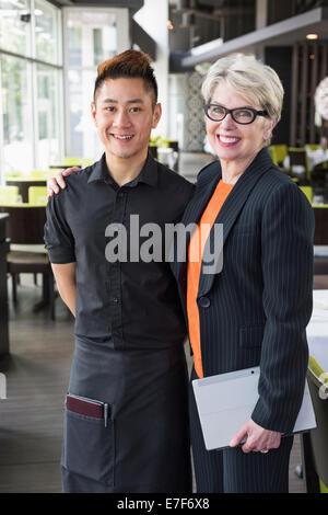 Businesswoman smiling in restaurant et de l'eau Banque D'Images