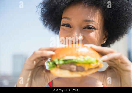 African American Woman eating cheeseburger Banque D'Images