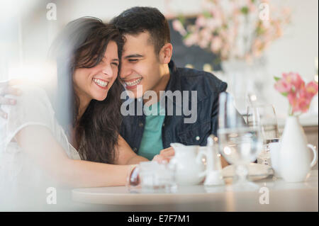 Hispanic couple laughing in cafe Banque D'Images