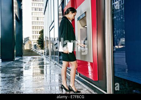 Mixed Race businesswoman using ATM en ville