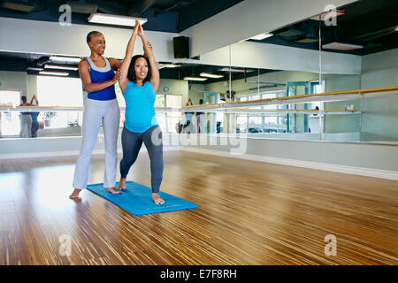 Femme travaillant avec professeur de yoga en studio