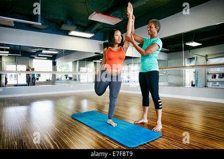 Femme enceinte travailler avec professeur de yoga en studio