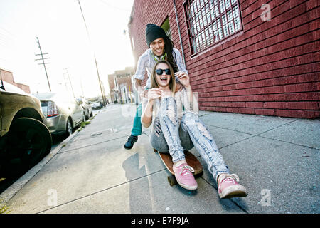Couple riding skateboard on city street Banque D'Images