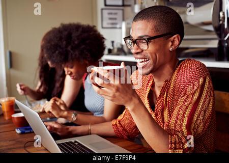 Les gens qui utilisent la technologie dans coffee shop Banque D'Images