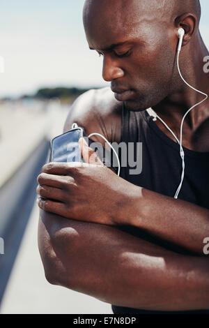 Musculaire de l'Afrique de l'athlète à l'écoute de musique. Modèle masculin à l'écoute de la musique sur son téléphone Banque D'Images